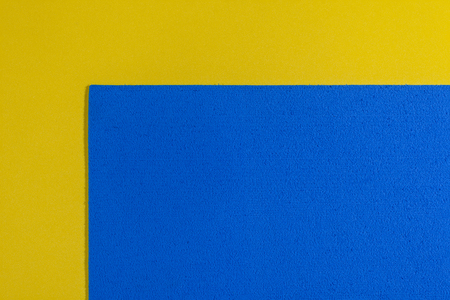 eva: Eva foam ethylene vinyl acetate sponge plush blue surface on lemon yellow smooth background Stock Photo