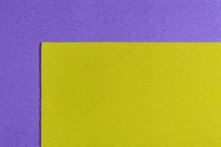 ethylene: Eva foam ethylene vinyl acetate lemon yellow surface on light purple sponge plush background Stock Photo