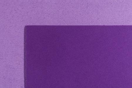 eva: Eva foam ethylene vinyl acetate smooth purple surface on light purple sponge plush background Stock Photo