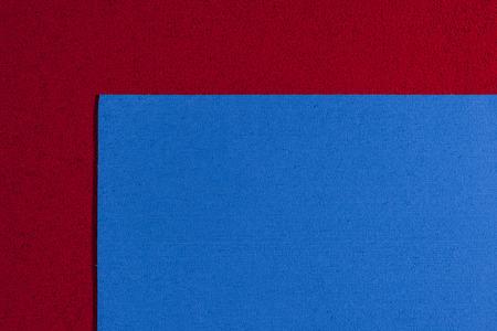eva: Eva foam ethylene vinyl acetate blue surface on red sponge plush background Stock Photo