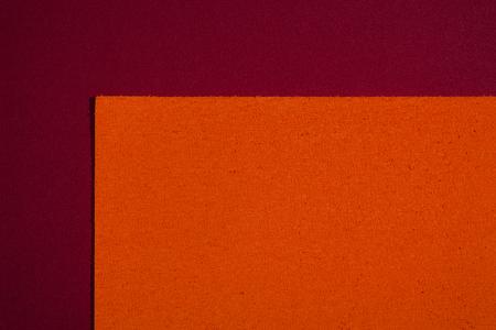 eva: Eva foam ethylene vinyl acetate sponge plush orange surface on red smooth background Stock Photo