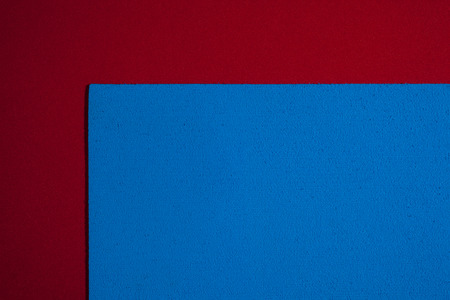 eva: Eva foam ethylene vinyl acetate sponge plush blue surface on red smooth background Stock Photo