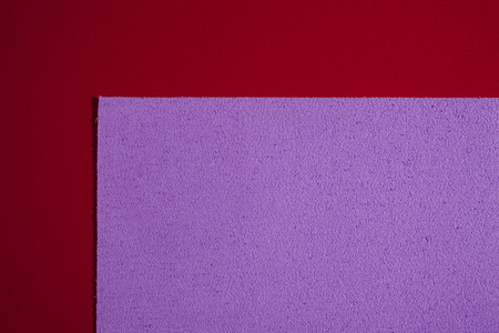 eva: Eva foam ethylene vinyl acetate sponge plush bright purple surface on red smooth background Stock Photo