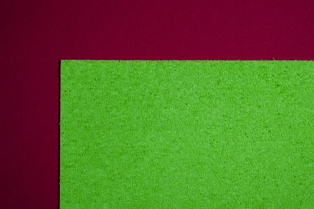 ethylene: Eva foam ethylene vinyl acetate sponge plush apple green surface on red smooth background Stock Photo