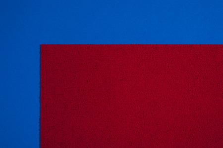 acetate: Eva foam ethylene vinyl acetate sponge plush red surface on blue smooth background Stock Photo