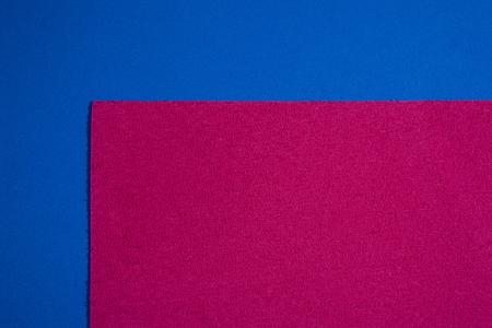 ethylene: Eva foam ethylene vinyl acetate sponge plush pink surface on blue smooth background Stock Photo