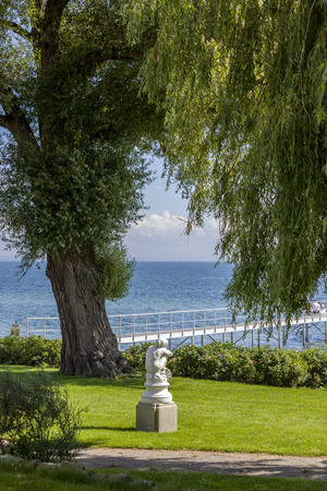 White marble sitting statue of a woman under a willowy tree looking at blue sea on sunny day