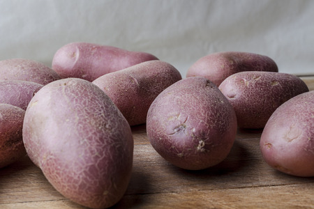 imperfect: Red big imperfect potatoes on wooden cutting board Stock Photo