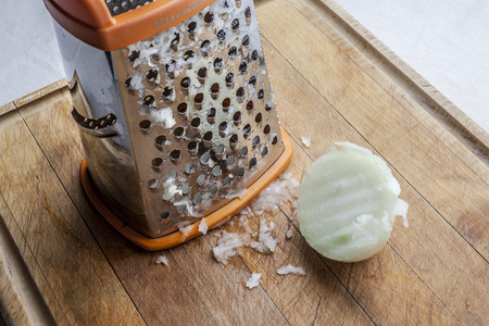 Half grated onion near metal standing grater on wooden cutting board Reklamní fotografie