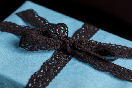 tied in: Closeup on black lace ribbon bow tied on wrapped in turquoise textured paper gift on black background
