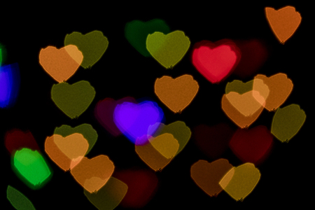 scattered in heart shaped: Bokeh vague colorful heart shaped scattered celebration lights on black background Stock Photo