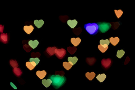 scattered in heart shaped: Bokeh vague colorful heart shaped small scattered celebration lights on black background Stock Photo
