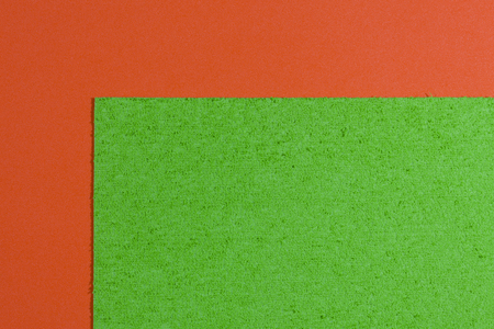 Eva foam ethylene vinyl acetate sponge plush apple green surface on orange smooth background Stock Photo