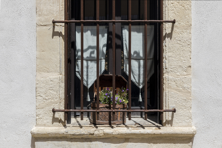 Stone french window with old box of violets on windowsill white curtains rusty iron bars Stock Photo