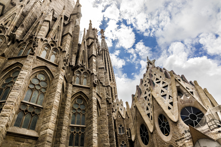View from low angle on side of Sagrada Familia with blue sky and white clouds
