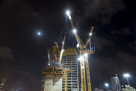 Construction building site with tower cranes building under construction lighted with projectors at night from low angle Stok Fotoğraf