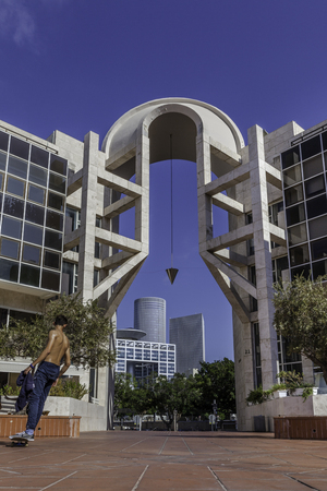 Young male skateboarder at Tel Aviv performing arts center gate with Azrieli buildings and haKirya Stock Photo