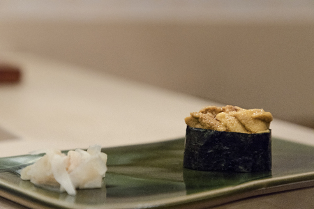 Urchin gunkan sushi served on green plate with ginger