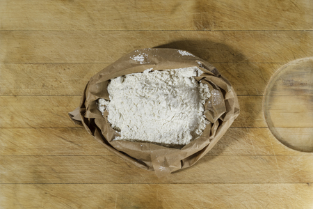 Brown paper sack of white flour in the center of rough wooden rectangular cutting board directly from above Banco de Imagens
