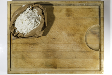 Brown paper sack of white flour in the corner of rough wooden rectangular cutting board on white background directly from above