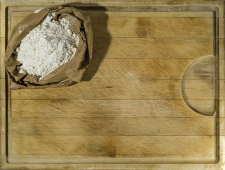 Brown paper sack of white flour in the corner of rough wooden rectangular cutting board directly from above