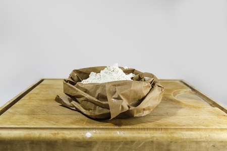 Brown paper sack of white flour in the center of rough wooden rectangular cutting board from side Banco de Imagens