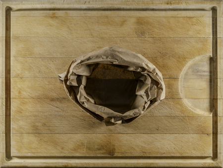 Brown paper empty sack on used wooden cutting board directly from above