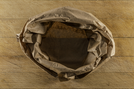 Brown paper empty sack on used wooden cutting board directly from above closeup