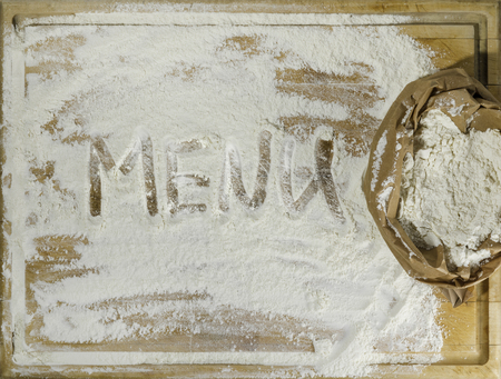 Rough wooden rectangular used cutting board background with paper sack of flour and menu word inscribed with finger directly from above Banco de Imagens