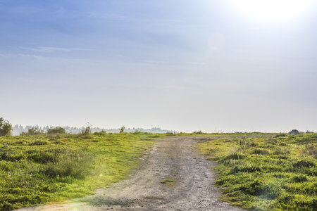 Ascending wide dirt road in a middle of a green lush blooming spring meadow slope with blue sky and dazzling sun Banco de Imagens