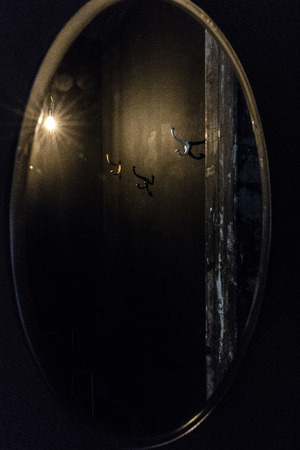 Black dressing room reflection in the oval mirror with gold frame with silver and gold pegs on the wall peeling door cant light bulb Banco de Imagens