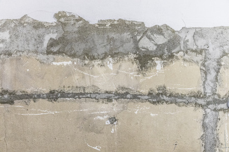 Rough peeled yellow orange gray concrete wall with putty patches background with whitewash strip Banco de Imagens
