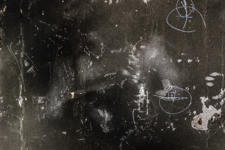 Rough black burned concrete wall background with whitewash scratches and chalk markings