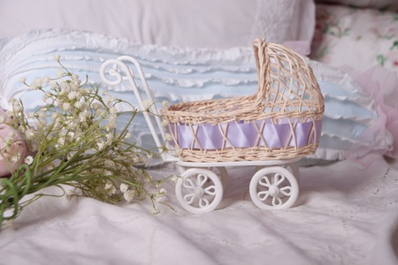 baby stroller: Baby stroller and spring bouquet composition on the bed Stock Photo