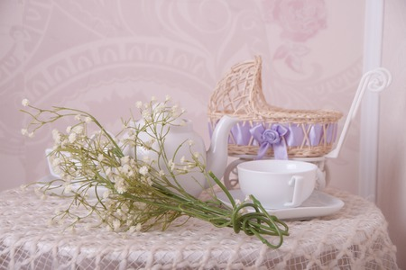 baby stroller: Baby stroller, tea cup and spring bouquet composition on the table