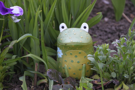 Frog Garden Statue. Decorative Figure Of Sitting Frog Among The Flowers  Stock Photo   56672905
