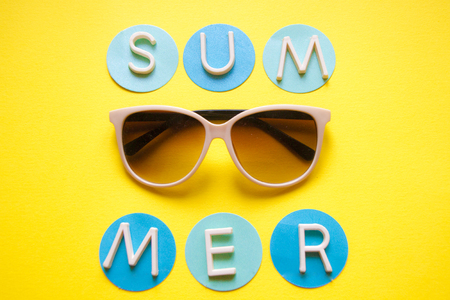 Sunglasses on yellow background and text summer. Top view. Holidays and vacation concept. Stockfoto