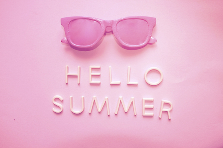 Sunglasses and text hello summer. Top view. Holidays and vacation concept in trendy monochrome pink colored photo