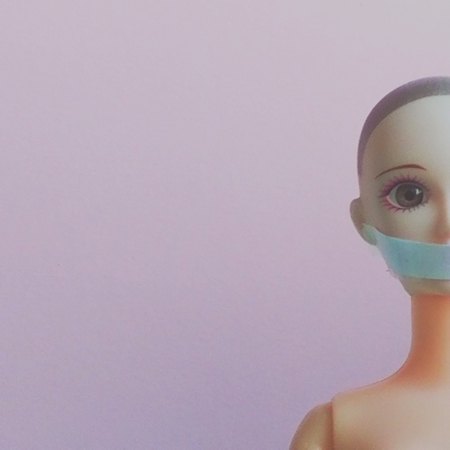 Doll face with sealed mouth. Concept photo for abuse, women rights, social issues theme