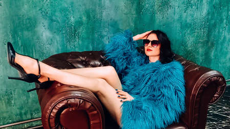 beautiful woman in colorful green fur coat and big sunglases sitting in chair in high heel shoes. Fashion studio photo