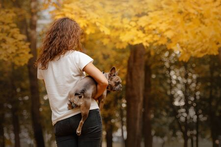 woman holding her french bulldog outdoors in autumn