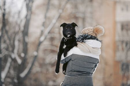 woman holding mixed breed dog in her arms outdoors in winter