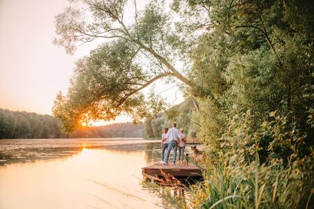 beautiful family with two dogs standing by the river at sunset, rear view Stock Photo