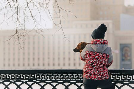 woman holding her dog in her arms outdoors in winter Stock Photo