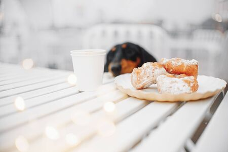 dessert buns and a cup of coffee on a street cafe table