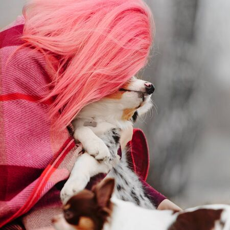 woman with pink hair hugging her puppy outdoors 版權商用圖片