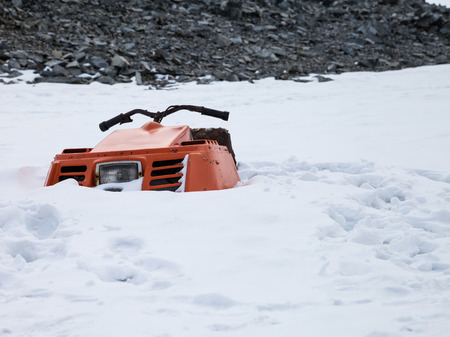 submerged: snowmobile submerged in the snow unusable