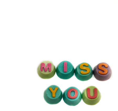 Letters chocolate miss you in Valentines Day on white background.