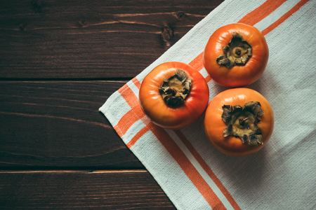 ripe persimmons on wooden table with napkin