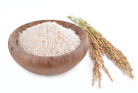 white rice on the wooden plate and rice plant , uncooked raw Stock Photo